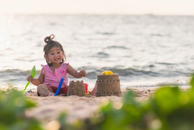 Happy fun asian child cute little girl playing sand with toy sand tools at a tropical sea beach in holiday summer on sunset time, tourist trip concept