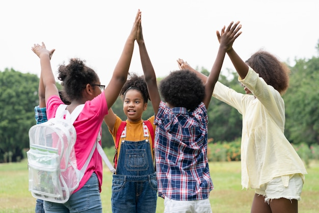 Happy fun group of african american children raised hands together in circle in the park