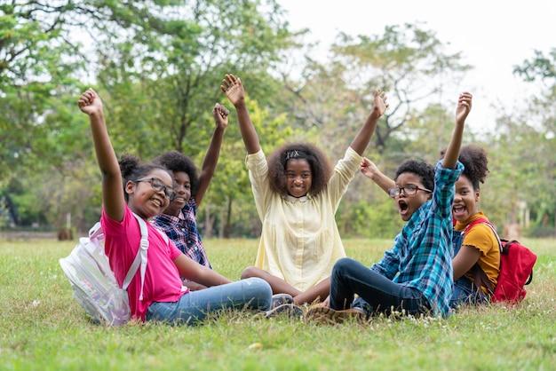 아프리카 계 미국인 어린이의 행복 재미 그룹 공원 교육 야외 개념에서 함께 손을 제기