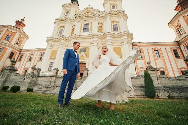 教会の近くの庭でポーズをとって幸せな楽しい新婚夫婦