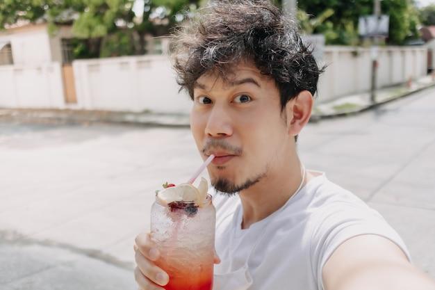 Happy funky hair man drinks italian soda syrup in hot sunny street of summer
