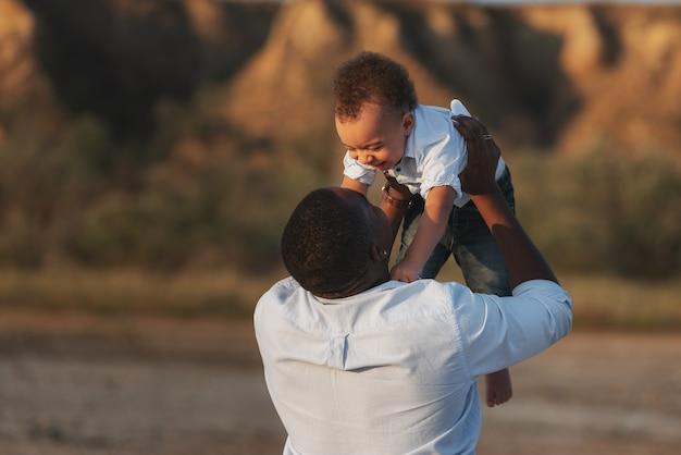 행복 한 재미있는 아프리카 계 미국인 유아 소년 아버지를보고 아버지 팔에 비행. 사랑하는 가족, 귀여운 작은 아이를 들고 단일 흑인 아빠