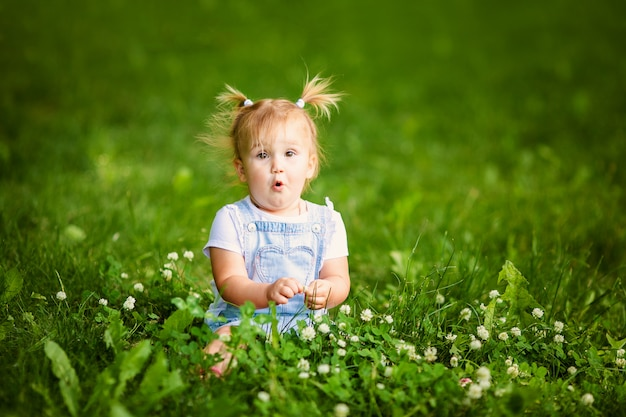 Happy funny baby girl with two little braids sitting on green grass