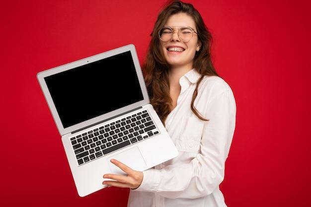 Счастливый смешной красивый брюнет вьющиеся молодая женщина, держащая компьютер ноутбук в очках белую рубашку с закрытыми глазами, изолированные на фоне красной стены. отрезать