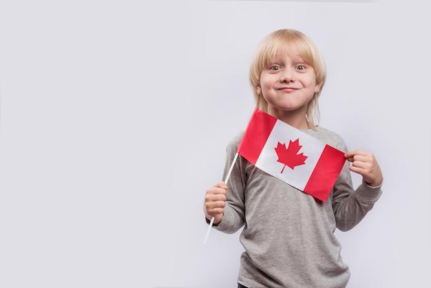 白い背景の上のカナダの旗を保持している幸せな面白い男の子。子供と一緒にカナダへの旅行。