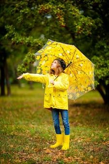 가 공원에서 고무 장화에 여러 가지 빛깔의 우산을 가진 행복 한 재미있는 아이 소녀.