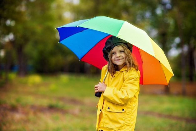 Happy funny child girl with multicolor umbrella in rubber boots at autumn park.
