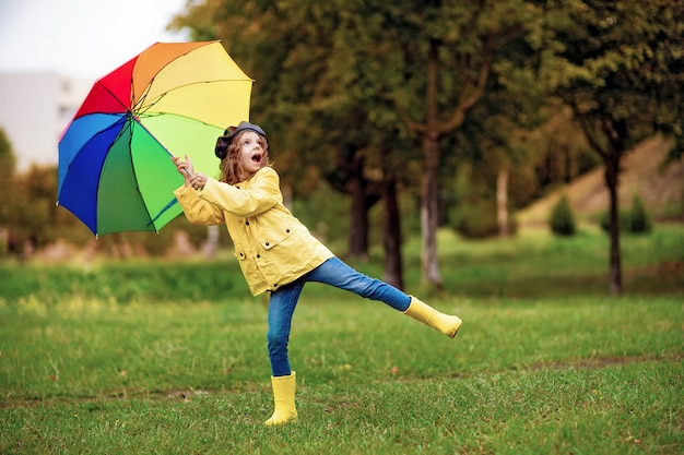 Happy funny child girl with umbrella in rubber boots