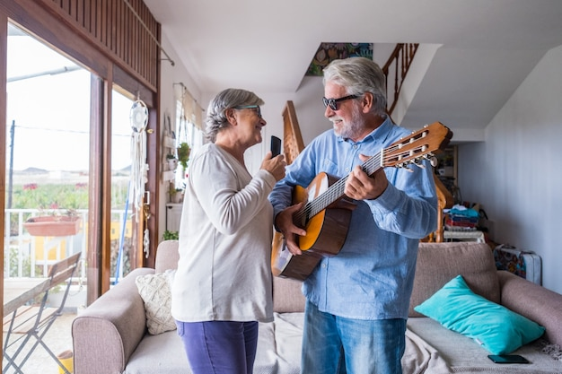 Happy and funny couple of old and mature people having fun and enjoying at home doing a party together singing and dancing playing the guitar indoor. holiday or event celebrating concept.