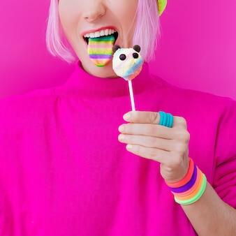 幸せな面白い女の子。お菓子が大好きです。パンダキャンディーとレインボー