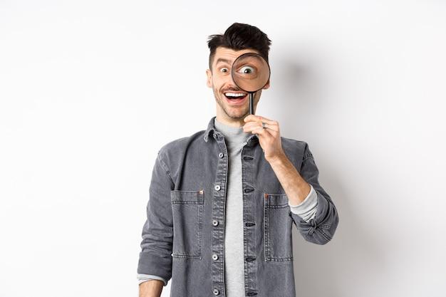 幸せな面白い男は大きな目で虫眼鏡を通して見て、面白い取引をチェックし、何かを検索し、白い背景の上に立っています。