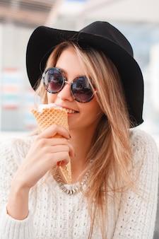 니트 스웨터에 우아한 검은 모자에 행복 재미 hipster 젊은 여자가 앉아서 여름 카페에서 달콤한 아이스크림을 먹는다. 매력적인 행복 귀여운 소녀.