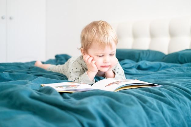 Счастливый смешной маленький мальчик в пижаме, читая книгу, лежа в кровати его родителей.