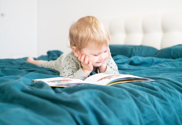 Счастливый смешной маленький мальчик в пижаме, читая книгу, лежа в постели своих родителей