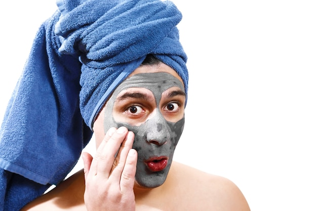 Счастливый забавный человек с маской для кожи, синее полотенце на голове, серьезный мужчина, мужчина балуется, изолированное фото,