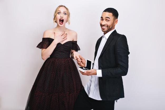 バレンタインデーを祝う素敵なかわいいカップルの幸せな面白い瞬間。豪華なドレスでびっくりした若い女性、白いシャツ、黒いジャケットでハンサムな男。サプライズ、プレゼント。