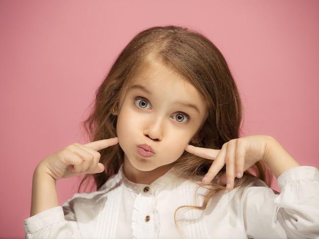 トレンディなピンクのスタジオの背景に分離された幸せな面白い十代の少女。美しい女性の肖像画。幼い子供の女の子。人間の感情、顔の表情の概念。正面図。