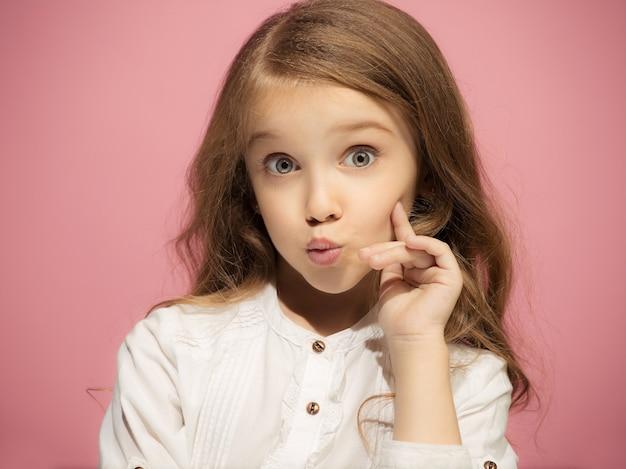 トレンディなピンクの壁に分離された幸せな面白い十代の少女。美しい女性の肖像画。幼い子供の女の子。人間の感情、表情の概念。正面図。