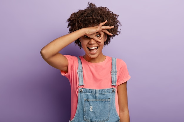 Happy funny woman looks through zero or okay gesture, holds rounded fingers near eye, smiles positively, peeps at something, feels overjoyed, wears pink t shirt and denim overalls, models indoor