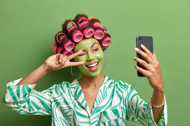 Felice donna divertente fa forme selfie segno di vittoria alla fotocamera dello smartphone sorride ampiamente gode di trattamenti per il visoapplica bigodini vestiti con abiti domestici casuali isolati sul muro verde