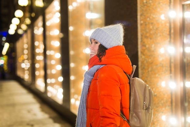 겨울 옷 배경 저녁 도시 조명 조명과 함께 행복 한 재미 있는 젊은 여자. 크리스마스와 겨울 휴가 개념입니다.