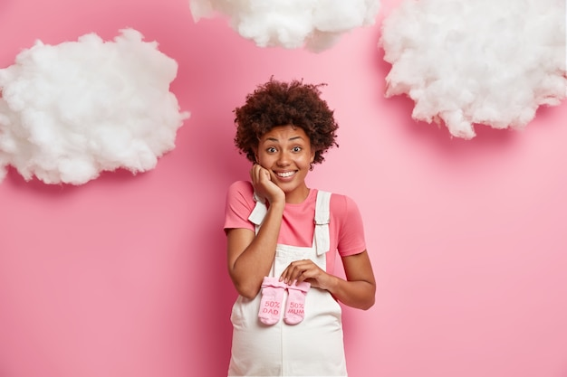 幸せな未来のお母さんは赤ちゃんを期待し、おなかの上にバラ色の子供靴下を持って、デニムのオーバーオールを着て、陽気な表情をして、ピンクの壁にポーズをとって、赤ちゃんの服を選びます。妊娠の概念