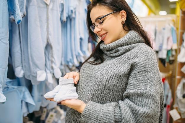幸せな未来のお母さんは、新生児用の店で子供服を購入します。