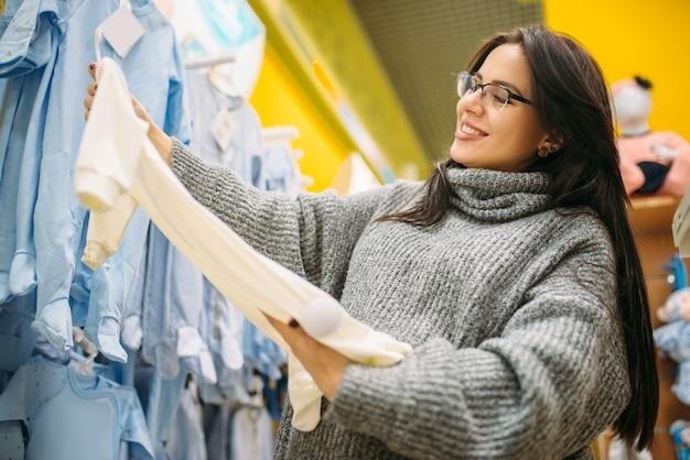 新生児の店で服を選ぶ幸せな未来の母親。乳幼児用品店の妊婦さん