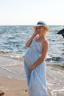 블루 프로방스 스타일의 드레스와 모자, backlite에서 바다 근처 포즈 행복 미래의 어머니