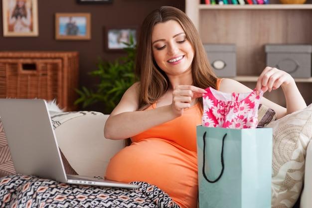 幸せな未来の母親は小さな女の子のための服を準備します