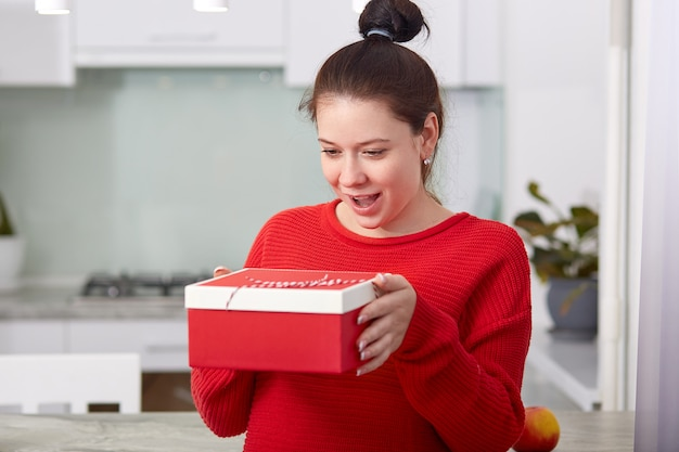 Happy future mother receives gift box from friend