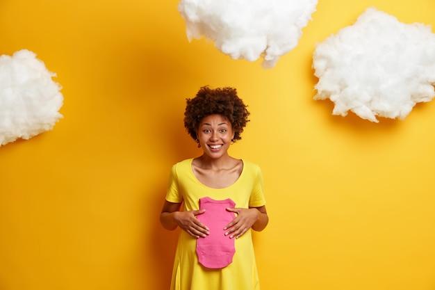 妊娠中の腹を持つ幸せな未来の母親は、胎児のためにバラ色の一重項を保持し、赤ちゃんを期待し、黄色のドレスを着て、上の白いふわふわの雲を着ています。母性、期待、妊娠の概念