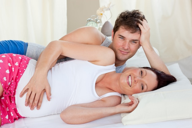 Happy future parents lying on the bed during the morning smiling at the camera