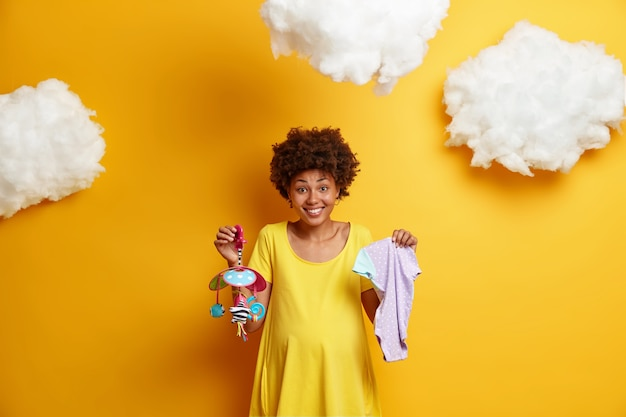 Happy fututre mother holds bodysuit and mobile for unborn child, dressed in yellow dress, being on last month of pregnancy, awaits baby, prepares for becoming mom, stands indoor. motherhood concept