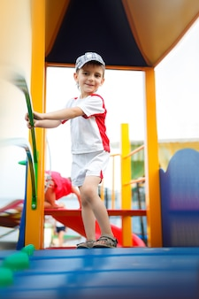 Happy games - pretty boy in cap on the playground