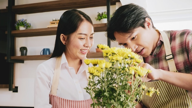Happy gardener couple taking care of yellow flowers together in the room.
