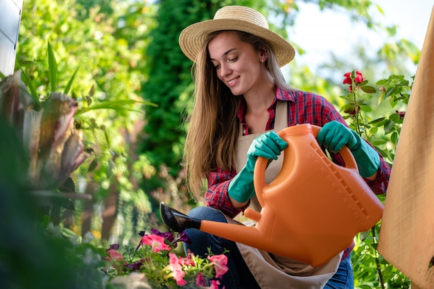 Happy gardener in hat and apron using watering can for watering flowers in home garden. gardening and floriculture