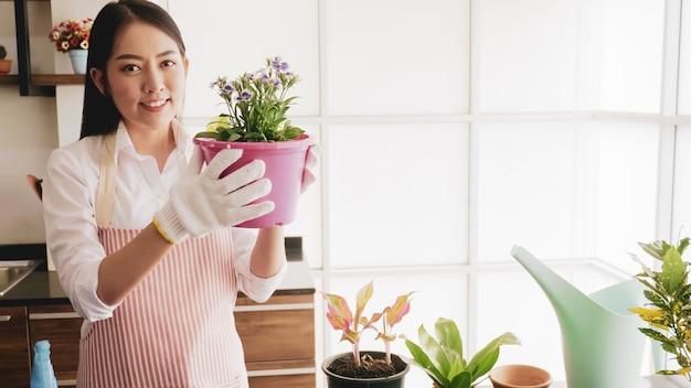 Happy gardener woman holding flowerpot in the room.