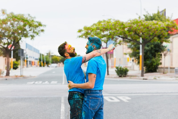 Happy gay couple hugging on road