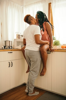 Happy gay couple kissing in the kitchen
