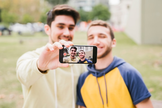 Happy gay couple shooting selfie on street