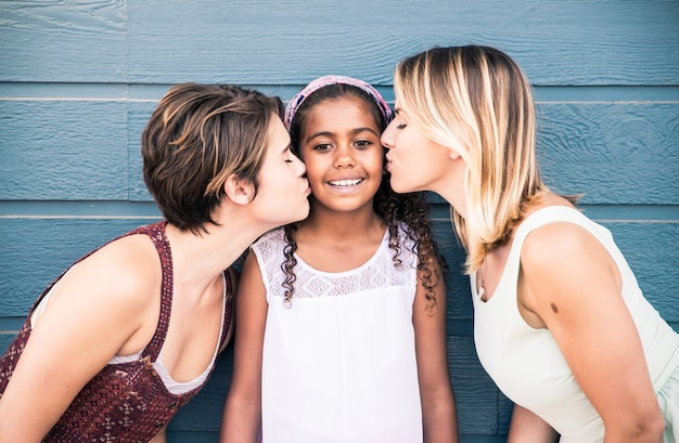 Happy gay couple spending time together with their adopted daughter