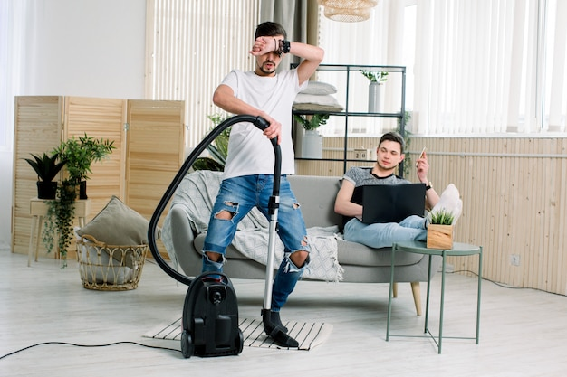 Happy gay man cleaning home, dancing with vacuum cleaner and having fun. housework, chores concept