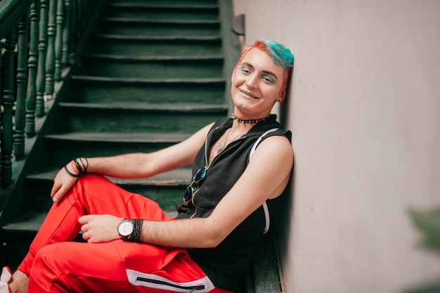 Happy gay man with colorful hairstyle in stylish clothes sitting on stairs.