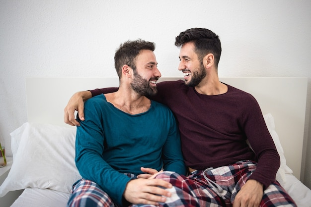 Happy gay men couple having tender moments together at home - focus on right man