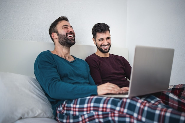 Happy gay men couple using laptop computer during lockdown isolation - focus on right man