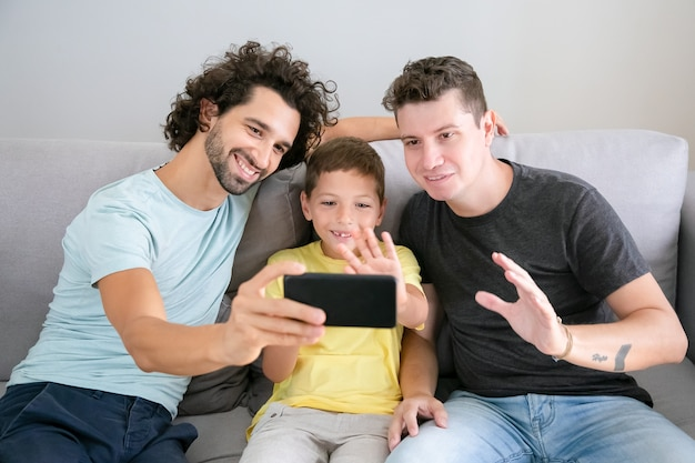 Happy gay parents and kid using cellphone for video call, sitting on couch at home, waving at frontal camera and smiling. front view. family and communication concept