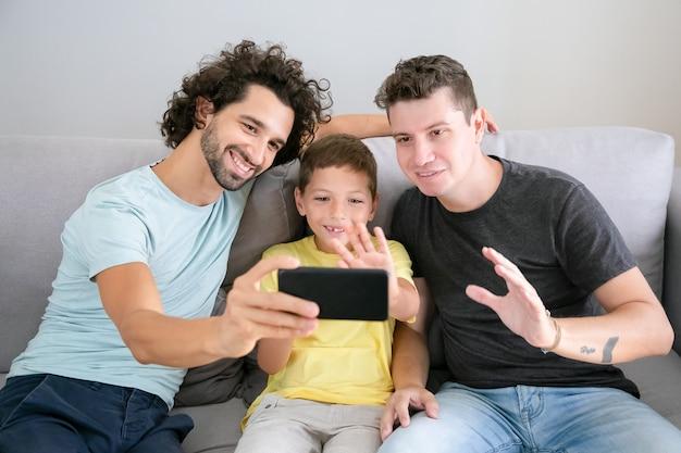 Genitori gay felici e bambino che utilizza il cellulare per la videochiamata, seduto sul divano a casa, salutando la fotocamera frontale e sorridente. vista frontale. famiglia e concetto di comunicazione
