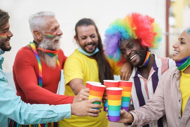 コロナウイルスの発生時に屋外のプライドでレインボーグラスで応援する幸せなゲイの人々