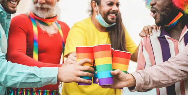 Счастливые геи приветствуют в радужных очках на открытом воздухе во время вспышки коронавируса